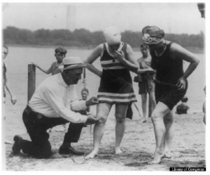 Historical photo of man measuring a womans bathing suit for modesty in the 1920s