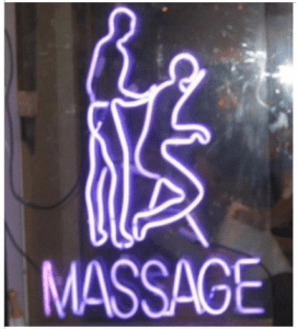 neon sign for chair massage in a shop window during the day