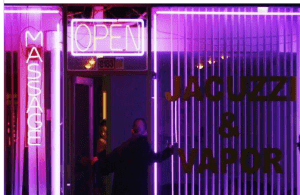 Picture of a neon sign for massage right next to a sign for jacuzzis
