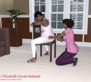 A pregnant woman sitting backwards on a chair while a Doula massages her lower back