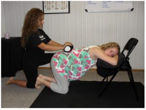 A Madriella student demonstrates how to use a rolling pin to massage the lower back