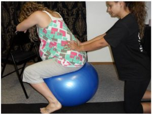 A Madriella student demonstrates how to massage the lower back while the client is sitting on a birth ball.