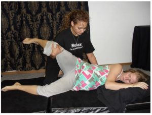 A Madriella student demonstrates how to assist a monther with stretching when she is in the side lying position