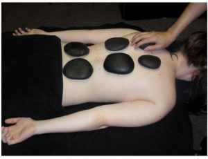 A photo showing the client with stones on her back